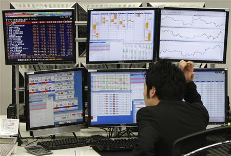Trader looks at monitors in a dealing room in Tokyo